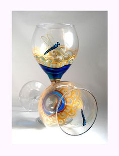 Hand painted whimsy in wine glasses. A hand painted Dragonfly in aqua blue flying over scrolled gold and silver blue fields. Each glassware goblet is with a unique swirling design in shimmering faux g