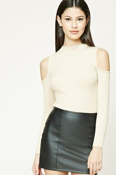A ribbed knit top featuring an open-shoulder, long sleeves, mock neck, and a form-fitting silhouette.
