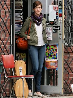 In character: The 30-year-old slipped on a khaki green coat and carried an orange bag on her shoulder for the part