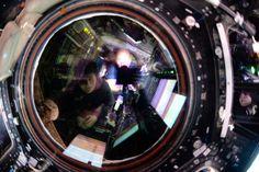 NASA astronaut Scott Kelly and ESA astronaut Samantha Cristoforetti reflected in circular lens watching spacecraft arrival