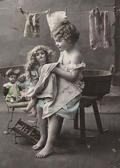 Antique photo of a girl with her dolls.