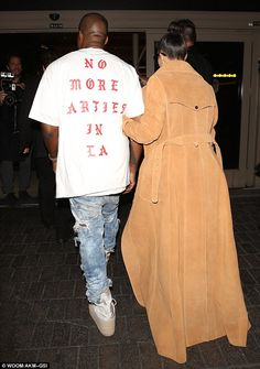 Attention-grabbing: The Life of Pablo artist wore a crew-neck sweatshirt with album track title No More Parties In LA emblazoned across the back, while his wife covered up her rear view in a floor-length coat