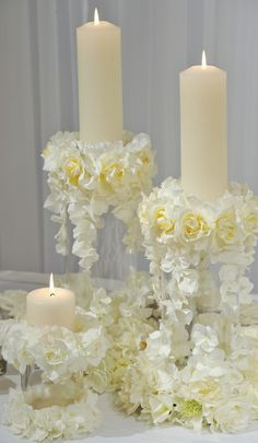 The white and yellow florals are decorated perfectly onto the candles, especially during a spring wedding.