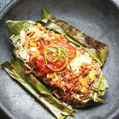 Nasi Bakar Indonesian Spicy Red Rice Wrapped In Banana Leaves and Grilled. Stuffed with Chicken, Pork, Salted Egg, Mushrooms.