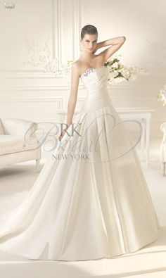 RK Bridal in NYC: White One Spring 2013 - Neis  A division of Pronovias. Strapless Royal Satin a-line ball gown with silver beaded applications. Shown with tulle veil style V-3705, sold separately.