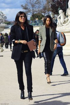 The Vogue Paris chief editor rocking a denim jacket / black blazer with Valentino leather and studded booties, low rise skinny jeans with a Balmain metal belt and chic editor Geraldine Saglio by her sidela modella mafia Emmanuelle Alt Fall 2013 fashion week street style 2