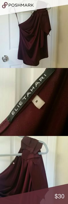 """Elie Tahari Silk OverTheShoulder Top Gorgeous, silk top is perfect for fall and holiday season events and happy hours! The color is a silky, port wine and has glam over one shoulder style with a """"crushed bow"""" and dangling sash. Worn twice and in great condition. Elie Tahari Tops Blouses"""