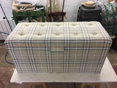 Ottoman blanket box. Upholstered in wool. Pattern matched buttons.