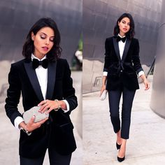 Feminine menswear: tuxedo blazer, white shirt, black bow tie, skinny black trousers, black heels, and silver clutch.