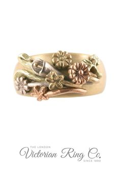 This ring design is inspired by the Victorian 'Language of Flowers'. The three-tone gold ring displays a bouquet of different flowers, lilies, daisies, forget-me-nots, chrysanthemum and the leaves of ivy and lilies. Each flower holds its own symbolism and has been hand carved and engraved. #LondonVictorianRing #LanguageofFlowers #FlowerSymbolism #VictorianRingDesign #JewelleryGiftIdeas #FloralRingDesign Engraved Wedding Rings, Victorian Engagement Rings, Country Rings, Full Eternity Ring, Jewelry Insurance, Ring Displays, Language Of Flowers, Conflict Free Diamonds, Chrysanthemum