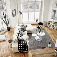 White sectional couch, gray rug, small circular coffee tables, black wire armchair, black and white accents