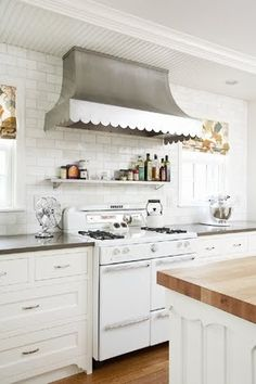 I love the custom scalloped stainless steel hood wall mounted onto white subway tiles over a vintage looking white range in a modern country style kitchen.