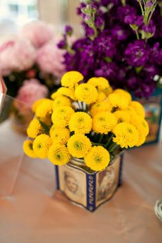 Antique tins with bright flowers make the perfect centerpiece for a happy #vintage #wedding.