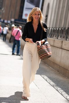City chic: Loose high-waisted cream wide-leg  trousers and a buttoned down black blouse