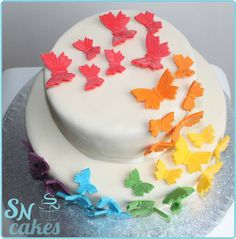 Two tier cake covered in white chocolate fondant and rainbow coloured fondant butterflies! [SNCakes.com]