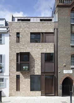 Brick and bronze paired for contemporary house on a historic London street.