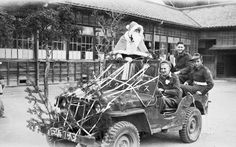 """Christmas at Miyajima School, 1946. Itsukushima, Japan. During the Christmas activities organised by 116th Australian construction depot, British Commonwealth Occupation Force (BCOF), at Miyajima school Santa Claus arrives by jeep. On the front of the jeep, inscribed in Japanese, are the words """"Merry Christmas"""". Left to right: VX150376 driver a. R. Davis, Euroa, Vic (1); SX34345 private M. P. Burgess, Norwood, SA (2); NX196391 Private C. R. Ansell, Willoughby, NSW (3)"""
