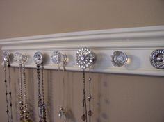 jewelry holder organizer featuring rhinestone center knob and total of 9 decorative  knobs on off white wood background 26 inches long. $45.00, via Etsy.