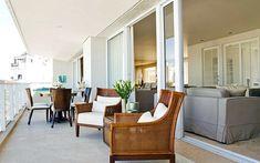 Portas corrediças integram a varanda à sala de estar e conferem elegância ao ambiente da decoradora Marília Veiga. Foto: Divulgação