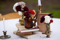 Vintage Jar Wedding Centerpiece | Flowers: Ranunculus, Roses, Seeded Eucalyptus, Thistle, Carnations | Colors: Red, Maroon, Ivory, Burgundy, Brass, Gold, Pink | Old Books | Candle Sticks | Root Floral Design