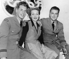 """MARLENE DIETRICH WITH TWO CANANDIAN PILOTS: Flight Lft Gerald H Bernier (left) and Flight Lft Kenneth J Fisher both of the RCAF posing at El Morocco with Marlene Dietrich of the HMBL (Hollywood's Most Beautiful Legs). Photo: Charles """"Chic"""" Farmer / El Morocco, 154 East 54th Street NY (December 1943)"""