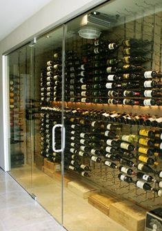 | P | Modern wine cellar room with glass door. Love the wooden cases of vintage wine.