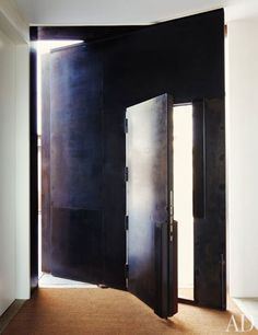 The front door is set into a rotating wall, creating a dynamic intersection of planes.  ***Clad the entry door in steel & the surrounding wall???***