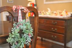 candle wreath hung on dining room chairs