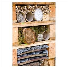 Bug hotel wall, inviting mason bees and ladybugs and more to come live in your yard. Insect hotels should be close enough to shrubs, trees, garden to provide food for them.