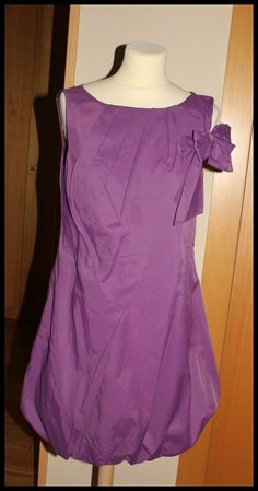 Vestido Morado, sin mangas abullonado, con detalle en lateral de lazo, una sola puesta. Marca STRENA, T M-L. 65%algodón, 35% nylon. PVP 64,99 eur.
