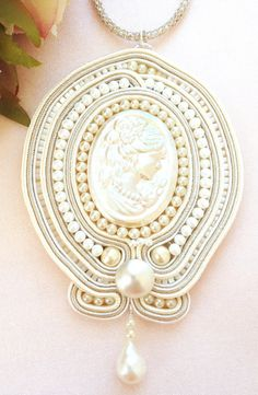 This romantic ivory soutache* embroidery pendant recalls Victorian days. It is a vintage carved mother of pearl cameo enriched with layers of