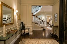 Madam Secretary- DC townhouse-- calm rug, spacious, gold touch, dim lighting, but open feeling with dark wood and stairway/living room visible