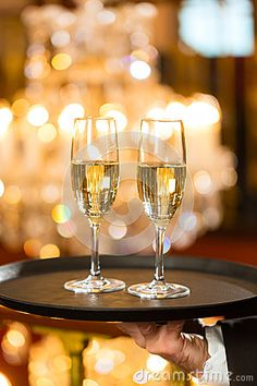 Waiter served champagne glasses on tray in restaurant by Arne9001, via Dreamstime