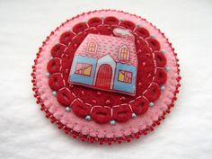 This lovely piece of wearable art is constructed of wool-blend felt, embellished with hand stitching and beading. It features an original hand drawn and painted illustration of a cute little blue house with a pink roof and smoking chimney. Crafted with care and great attention to detail, it can be worn as a brooch or as a pendant. Just put a piece of ribbon or your favorite chain through the felt loop on the back to wear as a pendant.    Approximately 2 1/2 x 2 1/2.    The illustration is…
