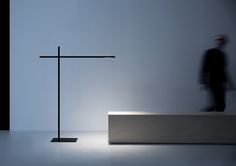 """Hashi is a floor lamp conceived to provide direct light in a simple and flexible manner. Its principle component is the pivot point between two """"chopsticks"""" (Hashi) that serve as light sources. The two sticks can be positioned in different ways, creating a strong, graphic effect in space. Particular care has been given to the proportions. The sticks always appear lightweight and balanced."""