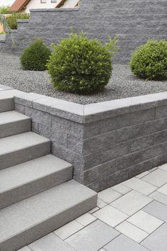 Harmonische Gesamtgestaltung der Außenanlage mit farblich abgestimmten Betonprodukten. Die York Mauer als Stützmauersystem, mit Kiesbeet und rund geschnittenen Buchsbaumkugeln ein minimalistisch-modernes Projekt. #rinnbeton #design #gartengestaltung