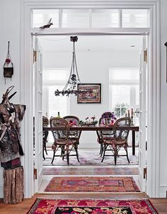Crazy fo this dining room:  wicker/bentwood chairs; French doors w/transom; chandelier (Christmas decorations); different oriental area rugs