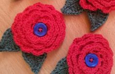 Red crocheted buttonholes with blue centres and green leaves - commissioned by a mother-of-the-bride-to-be for her daughter's wedding © LIsa Benjamin www.handmadeflowers.co.uk