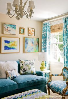 YES! A colorful living room!! More paint on the walls!!- F Schumacher Zenyatta Mondatta Fabric in Peacock bench ottoman tan walls blue velvet sofa gold blue toile French chair green double gourd lamp blue toile drapes layered bamboo roman shade eclectic art gallery