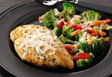 ~California Chicken~  4 small boneless skinless chicken breast halves (1 lb.);   3 cups frozen mixed vegetables,   (broccoli, red peppers and carrots), thawed, drained;   1/4 cup pesto;   1/4 cup water;   1/2 cup 2% milk shredded mozzarella cheese.