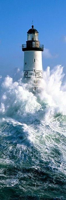 Leuchtturm im Meer, umgeben von brandenden Wellen