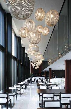 La hilera de lámparas hacen visualmente el techo más bajo, aportando ritmo y calidez a este espacio de líneas rectas que resultaría mucho más frío si ellas.