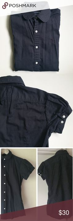 """Ralph Lauren Button Down Ralph Lauren Sport. Navy blue. Short, almost cap sleeves with two-button detail on back of sleeves. Peter Pan collar. Seven white buttons down front. About 22"""" long from top of shoulder to hem. About 17"""" from underarm to underarm. Tiny bleach spot in front, near bottom - see last image (no idea how it happened). Ralph Lauren Tops Button Down Shirts"""