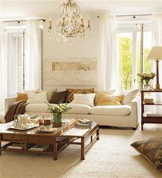 El salón, con el blanco como protagonista, gana calidez gracias a los muebles de nogal