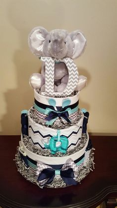 Blue, teal, and grey elephant diaper cake.  Baby shower centerpiece gift.  It's a boy! Check out my Facebook page Simply Showers for more pics and orders.   https://m.facebook.com/adorablegifts