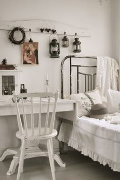 white cottage bedroom with painted wood surfaces and antique brass bed