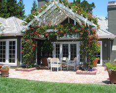 Excellent Pitched Roof Pergola To Complete Your Patio : Cute Pitched Roof Pergola Combined With White Armchairs And Red Flowers                                                                                                                                                                                 More