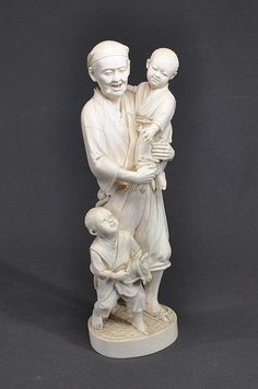 Lge early Japanese carved ivory group. Man carrying child, with another on hobby horse at his feet. Signature panel lost; but probably same artist as previous lot. Some age cracking. Height 34 cm