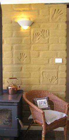 Feature bricks are layed upright in the wall. [Personalised mudbricks in wall. Note how pleasing the copper kettle and the wicker furniture look against the rustic lightly raked interior render.]