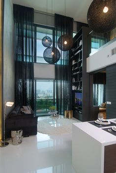 Double-high ceilings allow ample light and air into the space. The white reflective floor enhances the height of the room.